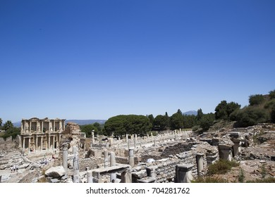An unusual view of the ruins of the ancient city of Ephesus, surrounded by hills, overgrown with trees and shrubs against the blue sky