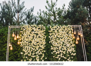 Unusual wedding ceremony arch with lots of white roses and retro lights