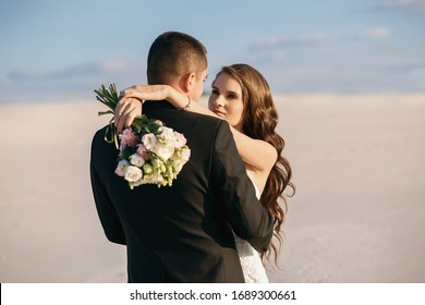 Unusual wedding photo shoot in the desert. Background of white sands at sunset. Happy brunette girl with long hair and a guy hug each other, the wedding couple enjoys each other