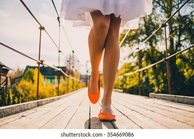 Unusual wedding shoes on the feet of the bride, bright orange, walk on he bridge in park. Fashion concept of  fresh, positive and bright autumn wedding.