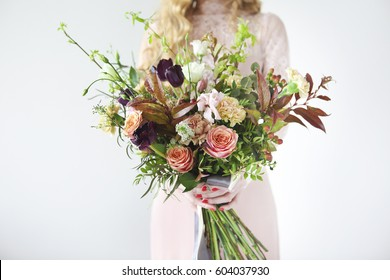 Unusual wedding stylish bouquet with orange and white flowers in hands of a bride
