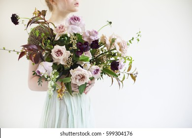 Unusual wedding stylish bouquet with pink and violet flowers in hands of a bride