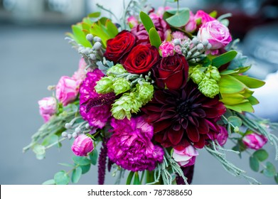 Unusual wedding stylish bouquet with pink flowers in hands of a bride