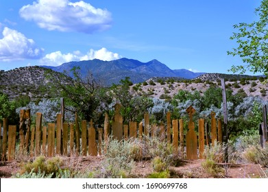 Unusual wooden fence faces a scenic view of the Sandia, Ortis, Jemez and Sangre de Cristo mountains ranges in New Mexico.