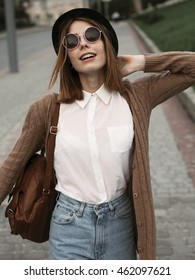 Unusual young woman with hat and sunglasses walking in the city