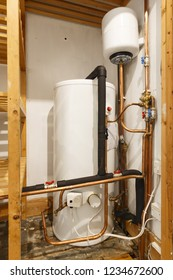 Unvented hot water cylinder and expansion vessel in an airing cupboard. UK plumbing