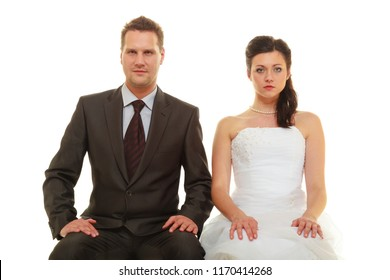 Unwanted marriage, bad life decisions concept. Serious groom in suit and bride wearing white dress sitting together and waiting for wedding, isolated.