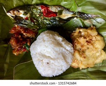 unwarpped steam rice with salted fish (pepes ikan peda), chilli paste (sambal terasi) and vegetable fritter on green banana leaf from West Java (Sunda), Indonesia