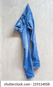 Unwashed blue jeans is hanging on the exposed concrete wall in bathroom.