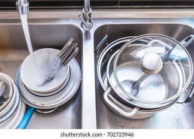 unwashed dishes, spoons, floks and pots in a kitchen sink with water flow