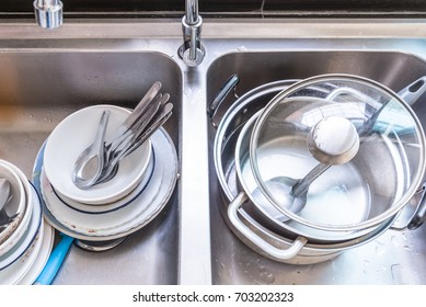 unwashed dishes, spoons, floks and pots in a kitchen sink