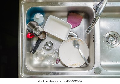 Unwashed dishes and utensils in a kitchen sink