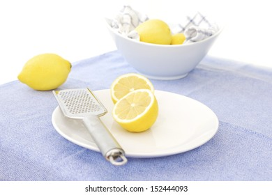 Unwaxed lemons on a plate with a lemon zester, and a bowl of lemons in the background