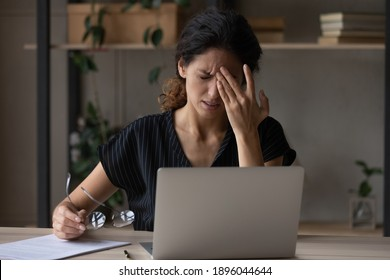 Unwell young Caucasian woman work on computer at home office take off glasses suffer from migraine or headache. Unhappy tired millennial female struggle with dizziness or blurry vision using laptop.