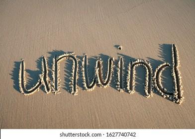 Unwind message handwritten in pristine brown sand with sun and shadows