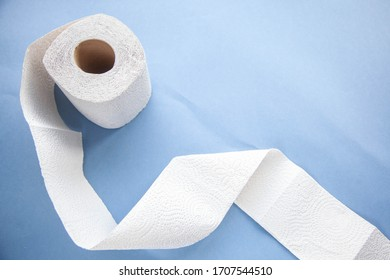 Unwinding toilet paper on a blue background. toilet paper deficiency coronovirus