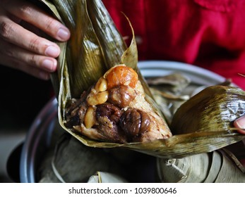 Unwrapping zongzi or rice dumpling by woman in red dress. Popular Asian food steamed sticky rice dumpling with sweet or savoury fillings wrapped in bamboo or reed leaves. (close up, selective focus)