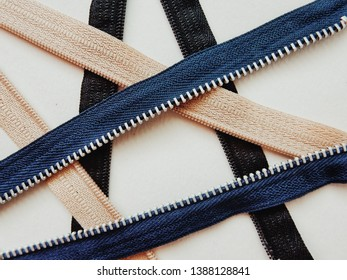 Unzip of black, blue and cream color zipper for background. It made from fabric for adhesive with dress, shirt, skirt and etc. and plastic for zipper adhesive with each side.