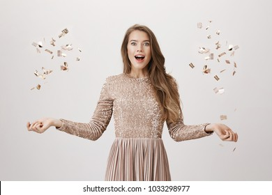 Upbeat attractive female model tossing golden confetti with spreaded hands, standing amazed or surprised in trendy evening dress over gray background. Girl was dancing when friends brought b-day cake