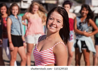 Upbeat Caucasian female teenager with smile near group of people