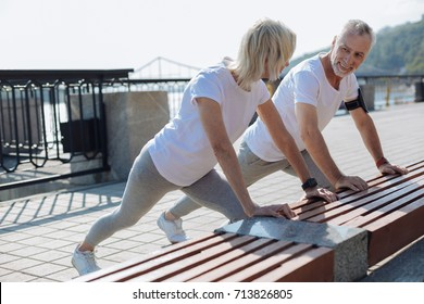 Upbeat couple doing stretching exercises together
