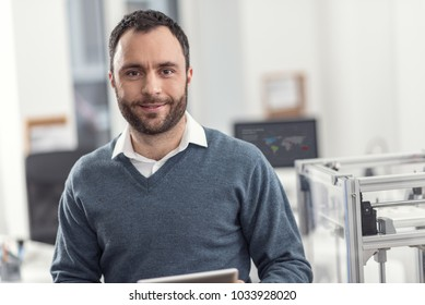 Upbeat worker. The portrait of a joyful young engineer standing near a 3D printer in his office, holding a tablet and posing for the camera, smiling pleasantly