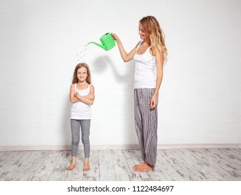 Upbringing child. Woman pours a child from a watering can. Nurture kids