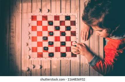Upbringing and development of children. The child plays checkers. Parents develop the child's intelligence. Deadlock, hopelessness, defeat concept.