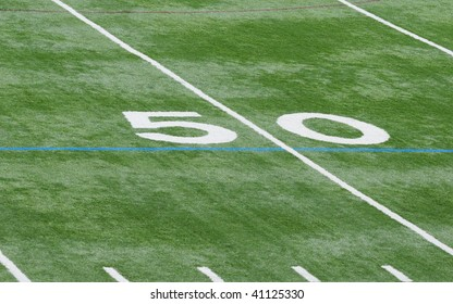 Upclose photo of the fifty (50) yard line on the football field.  No other numbers or objects appear.