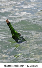 Up-close photo of green wine bottle with a message in it floating off the coast of Bermuda in the background.