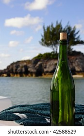 Up-close photo of green wine bottle on a boat with a message in it.  Island off the coast of Bermuda in the background.
