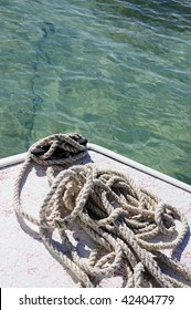 Up-close photo of rope and anchor tied to the front of a boat on the ocean in Bermuda