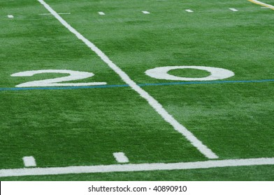 Upclose photo of the twenty (20) yard line on the football field.  No other numbers or objects appear.