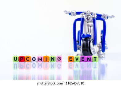 UPCOMING EVENT word block and miniature motorcycle concept on white reflection table