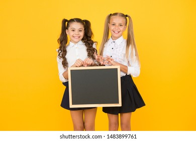 Upcoming events in school. Glad to inform. Schoolgirls informing you. School girls hold blank chalkboard copy space. Visual communication. Girls school uniform hold blackboard. Back to school concept.