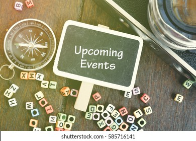 UPCOMING EVENTS word concept over top view flat lay,compass and vintage camera on wooden table with alphabetical block
