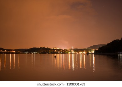 "Upcoming summer storm to Brno city during night over water reservoir known as ""Prygl"" dam. Orange clouds, reflection in water. South Moravia, Czech republic, Europe"