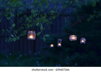 upcycled glass jars garden lanterns illuminated by candles hanging from tree branches in evening