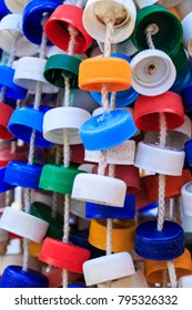 Upcycled rattle; multi-colored percussion instrument meant to be shaked. Made out of plastic bottle caps strung together, it is used by a professional percussionist in a Brazilian pop band.