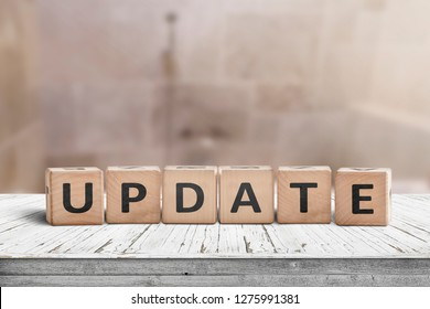 Update message sign on a wooden desk in a room with a blurry background