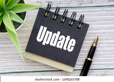 UPDATE text with decorative flower, fountain pen and notepad on wooden background. Business concept