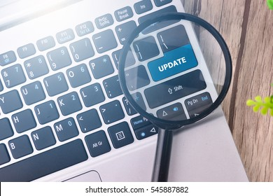 UPDATE word written on keyboard view with magnifier glass