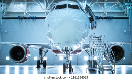 Up-Down Shot of a Brand New Airplane Standing in a Aircraft Maintenance Hangar. Plane's Door is Open and Ladder Stands Beside it.