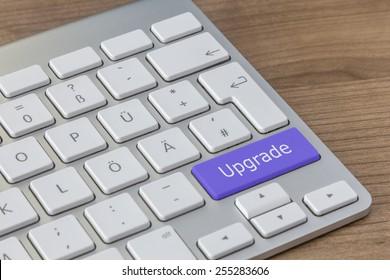 Upgrade written on a large blue button of a modern keyboard on a wooden desktop
