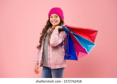 Upgrade your casual look with shopping. Happy girl hold shopping bags. Small child enjoy shopping. Cute little shopper pink background. Autumn sale. Shopping is her life.