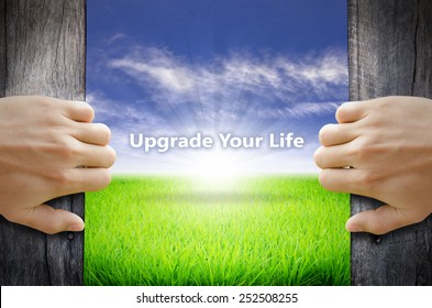 Upgrade your life motivational quotes. Hand opening an old wooden door and found a texts floating over green field and bright blue Sky Sunrise.