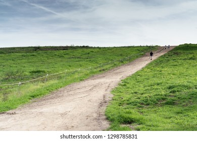 Uphill dirt hiking path with overcast sky. Green grass, small yellow flowers. Motion blur of people walking to the top.