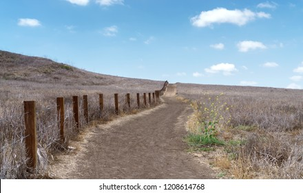 Uphill dirt hiking path through hills and dry brush. Wooden fence boundary. Wispy white clouds and blue sky. Copy space.