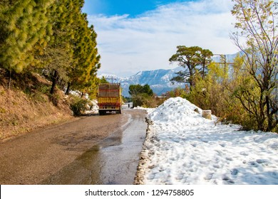 Uphill road in winter at banikhet dalhousie himachal pradesh india. Scenic winter view from the asphalt road covered with snow and treess on the side of road on blue sky background and clouds