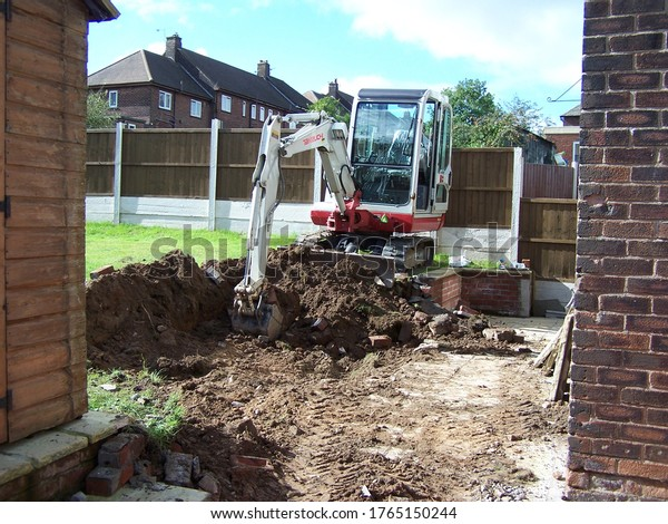 Upholland, Lancashire, England, 28/06/2020, Workman using a mini digger to excavate a hole for extension footings in a garden lawn with green grass